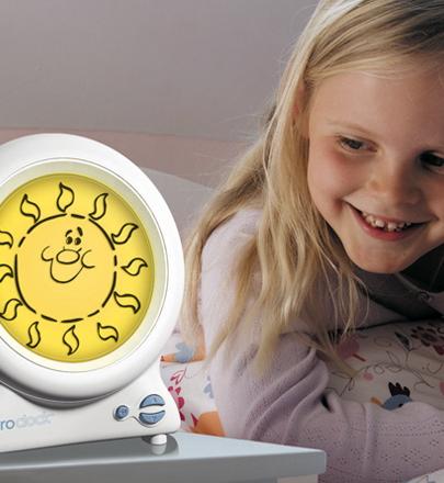 child smiles at yellow sun on gro clock